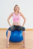 Denkende blonde schwangere Frau, die auf Übungsball sitzt Stockbilder