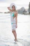 Denkende blondevrouw in het witte strandkleding stellen die weg eruit zien Stock Foto