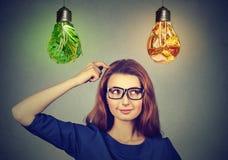 Denkende Entscheidung der Frau auf der Diät, die oben Glühlampen des Gemüses der ungesunden Fertigkost betrachtet Stockfotos
