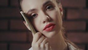 Denkende Frau, die Geldstapel nahe Gesicht hält und Kamera untersucht stock video footage