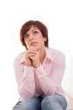 Denkende Frau, die oben mit der Hand auf Kinn schaut Stockfotografie