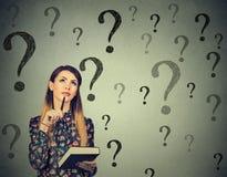 Denkende Frau, die oben viele Fragezeichen betrachtet Lizenzfreie Stockfotografie