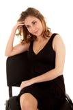 Denkende Frau in einem schwarzen Kleid auf einem Stuhl lizenzfreie stockfotos