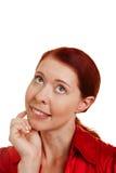 Denkende Frau mit der Hand auf Kinn Stockfotografie