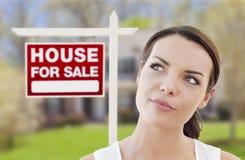 Denkende Frau vor Haus und für Verkaufs-Zeichen stockfotografie