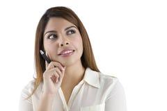 Denkende hispanische Frau, die eine Feder anhält Lizenzfreies Stockfoto