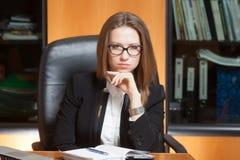 Denkende jonge mooie vrouw in bureau Royalty-vrije Stock Afbeelding