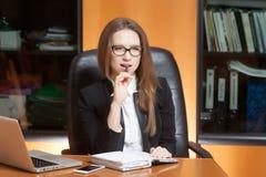 Denkende jonge mooie vrouw in bureau Royalty-vrije Stock Fotografie