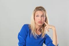 Denkende junge blonde Frau, die weg mit Index auf Backe schaut Stockbild