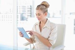 Denkende junge blonde Geschäftsfrau, die einen Tabletten-PC verwendet Stockfotografie
