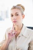 Denkende junge blonde Geschäftsfrau, die Kamera betrachtet Lizenzfreies Stockfoto