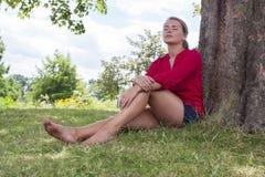 Denkende junge Frau, die Sommerfrische unter einem Baum genießt Stockbilder