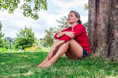 Denkende junge Frau, die unter einem Baum für Sommerfrische sitzt Lizenzfreie Stockfotografie