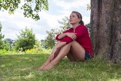 Denkende junge Frau, die unter einem Baum für Sommerfrische sitzt Stockfotografie