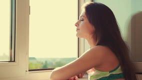 Denkende junge Frau, die vom Fenster und vom Genießen der Luft schaut
