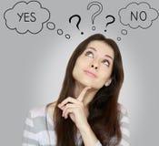 Denkende junge Frau mit ja oder nein Lizenzfreie Stockfotografie