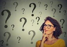 Denkende junge Geschäftsfrau in den Gläsern, die oben vielen Fragezeichen betrachten Stockbilder