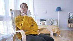Denkende mittlere Greisin, die auf dem zufälligen Stuhl, lösend sitzt gedanklich lizenzfreie stockfotos