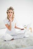 Denkende nette blonde tragende Haarlockenwickler unter Verwendung des Laptops Stockfoto