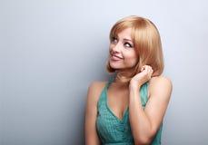 Denkende nette junge blonde Frau, die oben schaut Lizenzfreie Stockfotos
