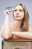Denkende sexy blonde Frau, die alte Audiokassette hält Stockfotografie