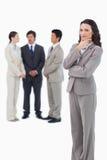 Denkende Verkäuferin mit Team hinter ihr Lizenzfreie Stockfotos
