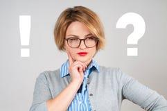 Denkende vrouw met het vragen van teken en uitroepteken Stock Afbeeldingen