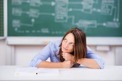 Denkende Vrouwelijke Leraar Chin Sitting At Desk royalty-vrije stock foto's