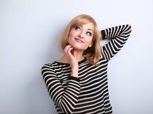 Denkende zufällige blonde Frau, die das Kinn und das entspannende Klo verkratzt Stockbild