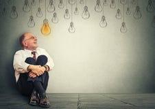 Denkender älterer Mann in den Gläsern, die auf dem Boden oben schaut mit heller Ideenbirne über Kopf sitzen Stockfoto