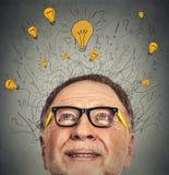 Denkender älterer Mann mit Fragenzeichen und helle Ideenbirne über Kopf Stockfotos