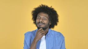 Denkender afroer-amerikanisch Mann mit neuem Plan auf gelbem Hintergrund stock footage