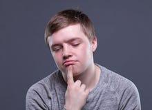 Denkender blonder junger Mann Stockfotos