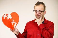 Denkender erwachsener Mann, der defektes Herz hält lizenzfreie stockfotografie