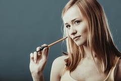 Denkender Griffstift des blonden Mädchens auf grauem Hintergrund Stockfoto