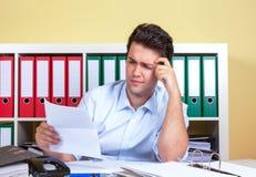 Denkender hispanischer Kerl im Büro mit einem Buchstaben in seiner Hand Stockfoto
