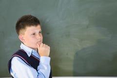 Denkender Junge an der Tafel Lizenzfreies Stockbild