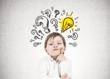 Denkender kleiner Junge, Fragezeichen, Idee stockfoto