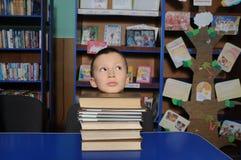 Denkender Lügenkopf des Jungen auf dem Stapel von Büchern in der Bibliothek, Kopf auf Stapel des Buches setzend lizenzfreie stockfotografie