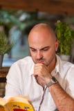 Denkender Mann, der ein Buch liest Lizenzfreies Stockfoto