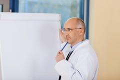Denkender reifer Doktor Standing Near Flipchart Lizenzfreie Stockbilder