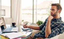 Denkender Student beim Sitzen an seinem Schreibtisch Lizenzfreies Stockfoto