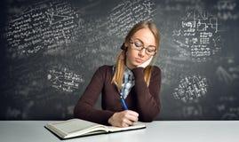 Denkender Student, der an einem Schreibtisch sitzt Lizenzfreie Stockfotografie
