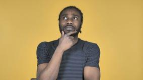 Denkender zufälliger afrikanischer Mann mit neuem Plan lokalisiert auf gelbem Hintergrund stock video footage