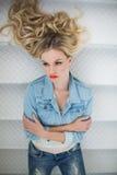 Denkendes blondes tragendes Denim kleidet das Lügen auf Treppe Stockfotos