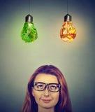 Denkendes Glühlampen der ungesunden Fertigkost und des grünen Gemüses oben betrachten der Frau Stockbild