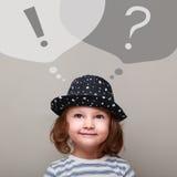 Denkendes glückliches Kindermädchen, das oben auf Fragen- und Ausrufszeichen schaut Lizenzfreie Stockbilder