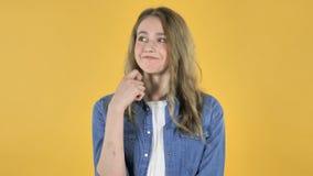 Denkendes junges hübsches Mädchen erhielt neue Idee auf gelbem Hintergrund stock video footage