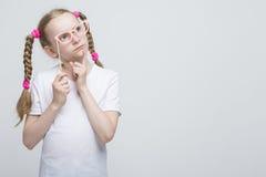 Denkendes kaukasisches blondes Mädchen mit den Zöpfen, die mit künstlerischen Schauspielen aufwerfen Lizenzfreies Stockbild