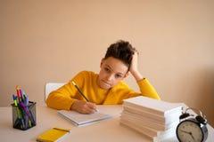 Denkendes Kind bohrte, frustriert und seine Hausarbeit oben tun eingezogen stockfoto